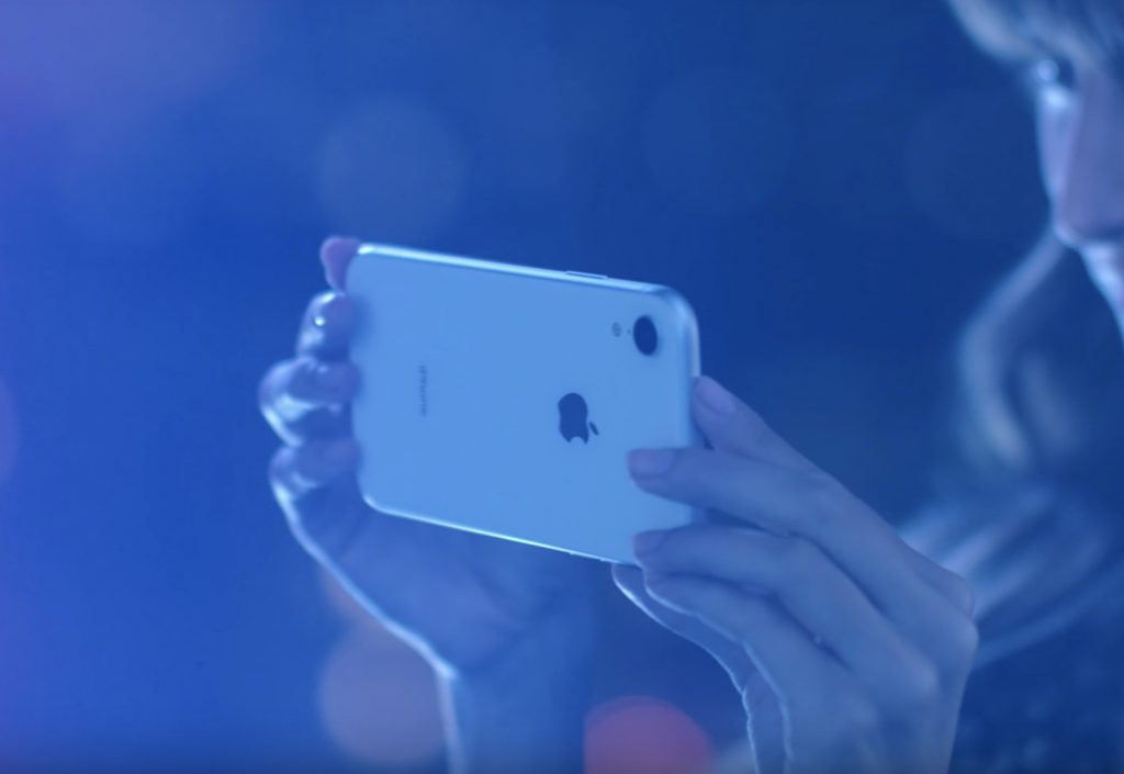 Picture of a woman holding an iPhone XR in white.