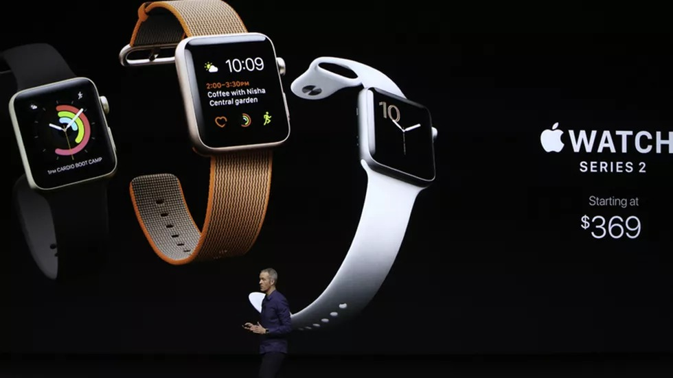 Apple event with Apple Watch Series 2 pricing on display.